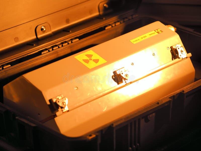 Envase encajonado del metal con la advertencia de la radiación en una caja militar del transporte del grado bajo luz roja imágenes de archivo libres de regalías