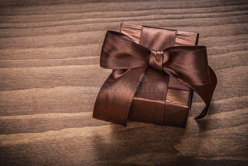 Envase reluciente encajonado del regalo en el tablero de madera del vintage imagen de archivo libre de regalías