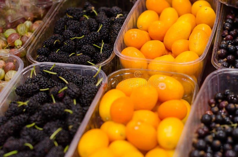 Envases con las diversas bayas y fruta maduras en el mercado fotos de archivo