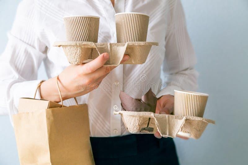 Envases femeninos del café de la tenencia, envases del withfood de la bolsa de papel Entrega de la comida y del café fotografía de archivo