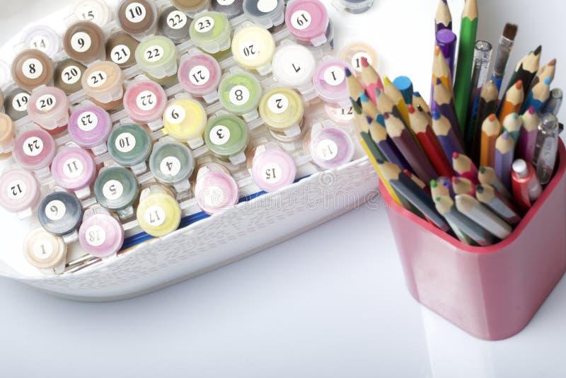 Envases numerados con las pinturas y los cepillos de diversos tamaños Para dibujar por números En un envase en un fondo blanco de imagenes de archivo
