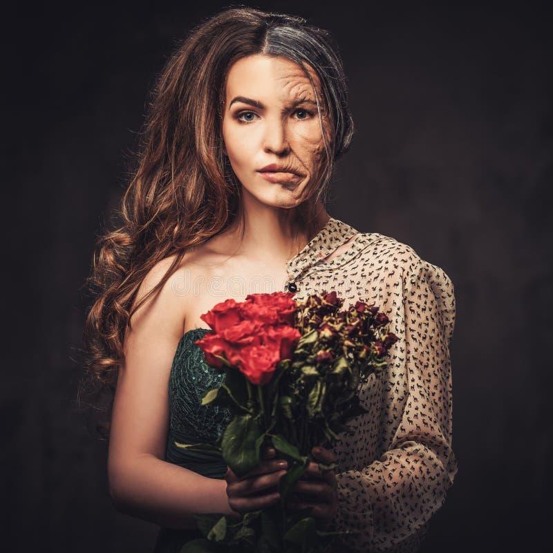 Envejecimiento, concepto del cuidado de piel Media vieja media mujer joven con el ramo de rosas rojas fotos de archivo libres de regalías