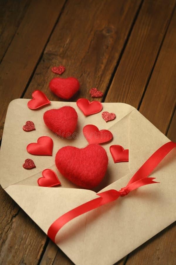 Envelop en vele rode harten op rustiek hout stock afbeelding