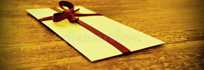 Envelop met rood lint, gift stock afbeeldingen