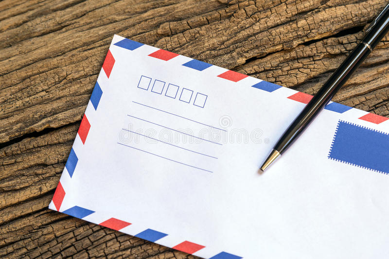 The envelop and the pen. On the wooden background table royalty free stock image