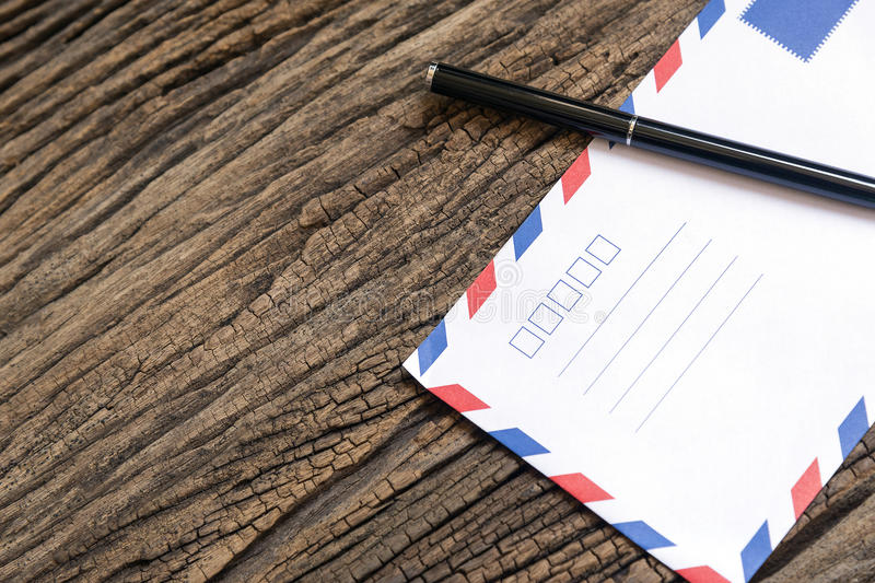 The envelop and the pen. On the wooden background table stock image