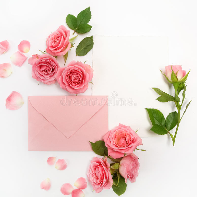 Envelop with white card and rose background. Top view. Flat lay royalty free stock photography
