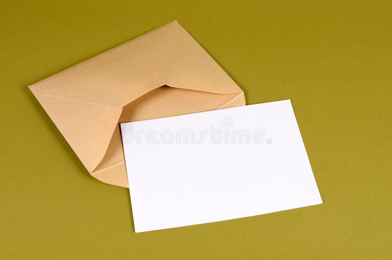 Brown envelope, blank note card paper or letter, copy space. Metallic gold envelope with blank message card letter or invitation isolated on a green background royalty free stock image