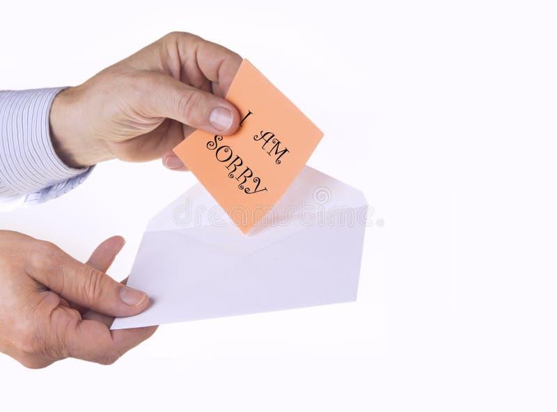 Envelope branco com nota de papel com mão do homem no fundo branco Eu sou conceito pesaroso fotografia de stock royalty free