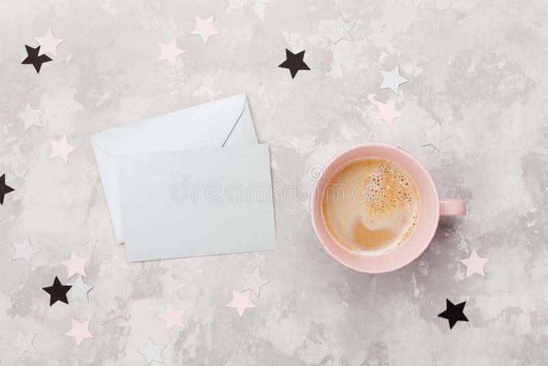 Envelope com cartão vazio e xícara de café na opinião do desktop do funcionamento da mulher Configuração lisa Convite do partido  imagem de stock