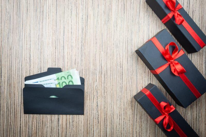 Envelope com o euro- dinheiro e presente três na tabela de madeira Escolha dif?cil da doa??o Copie o espa?o foto de stock royalty free