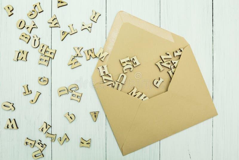 Envelope de papel aberto do correio com letras de madeira dispersadas para dentro em uma tabela branca imagens de stock