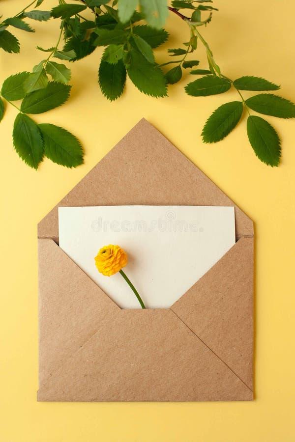 Envelope de Papercraft com um arranjo de flor do amarelo da mola Configuração lisa, vista superior foto de stock