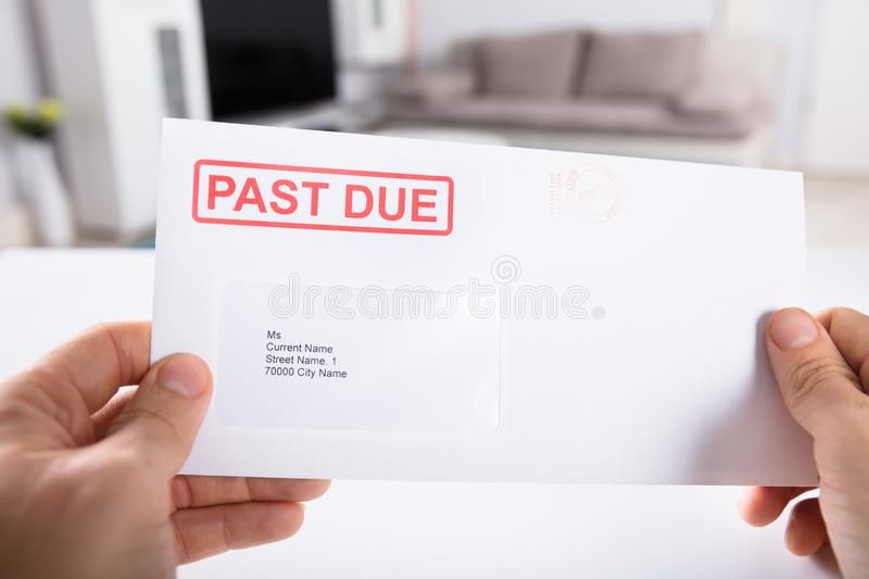 Envelope de Person Holding Past Due Bill foto de stock