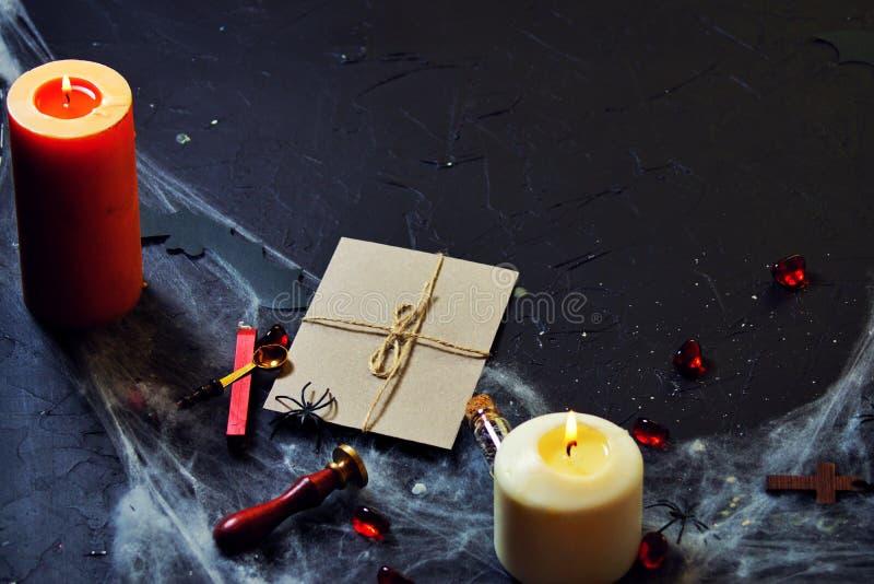 envelope de safra com carimbo queimando velas e aranhas na internet ao lado de uma cruz de madeira fotografia de stock