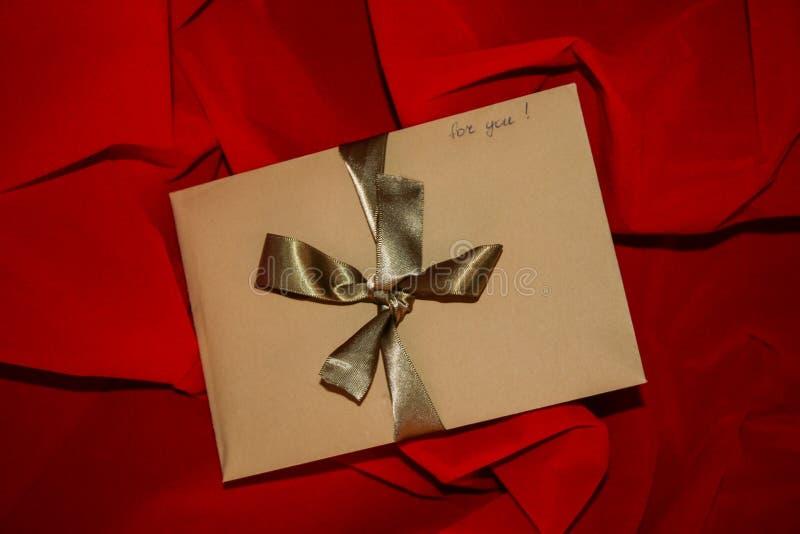 Envelope do ofício do presente do dia de Valentim com fita e sinal dourados 'para você 'no fundo vermelho imagens de stock royalty free