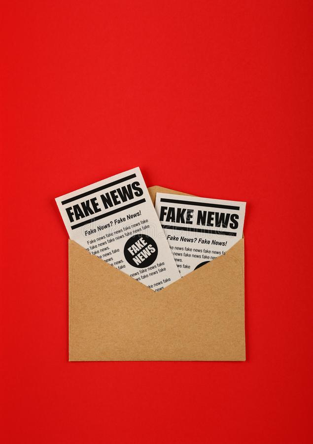 Envelope with FAKE NEWS newspapers over red. Close up brown paper mail envelope with FAKE NEWS newspapers over red background with copy space, elevated top view stock photo