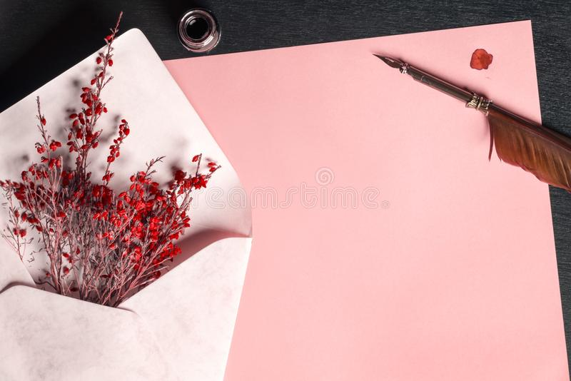 Envelope with flowers on a paper and a quill pen royalty free stock photography