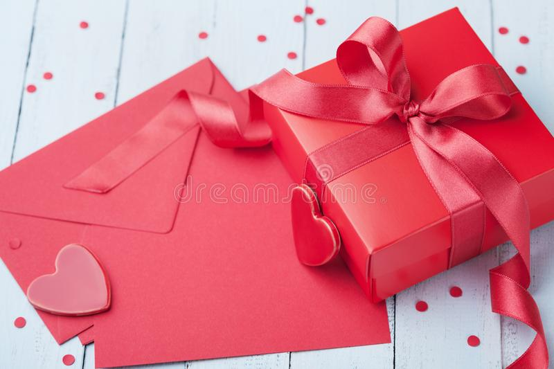 Envelope, gift, paper card and red heart on blue table for greeting on Valentines Day. royalty free stock images