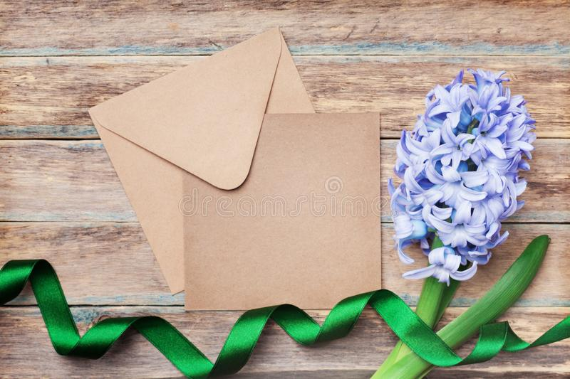 Envelope, hyacinth and ribbon on wooden vintage table top view. Happy Mothers Day holiday greeting card with flowers. stock photos