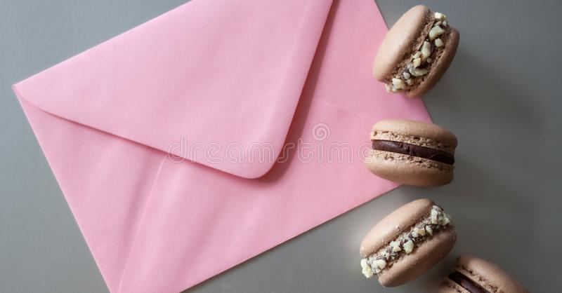 Envelope and macarons. Pink envelope and dark chocolate macarons on silver background stock image