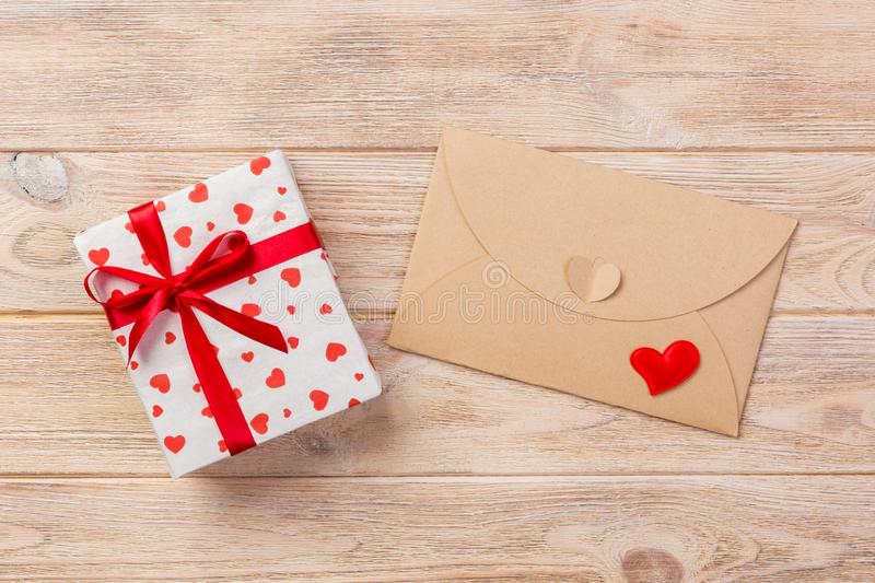 Envelope Mail with Red Heart and gift box over Orange Wooden Background. Valentine Day Card, Love or Wedding Greeting Concept.  stock images