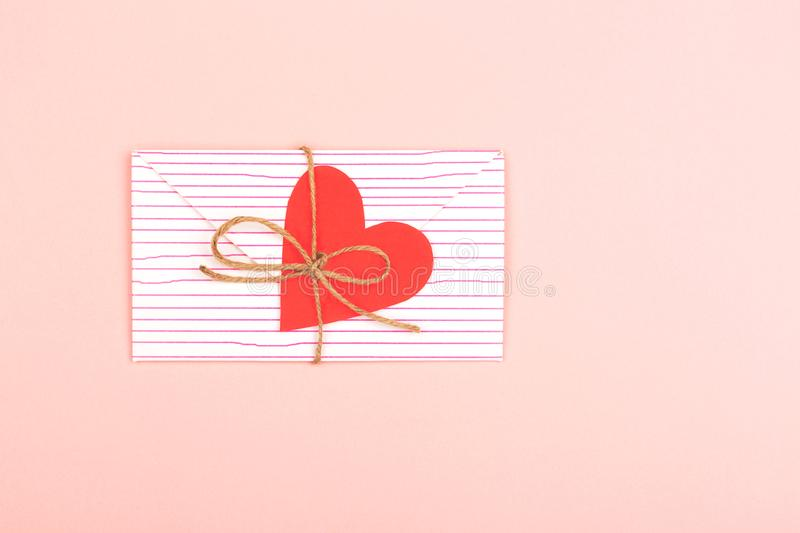 Envelope on pink background. Creative love or Valentine day background made with cute envelope, heart shape paper and rope. Love letter or message concept stock photo