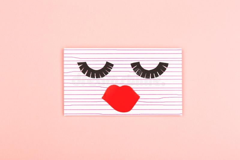 Envelope on pink background. Creative love or Valentine day background made with cute envelope. Eye lashes and red lips looklike a woman face. Love letter or royalty free stock photography