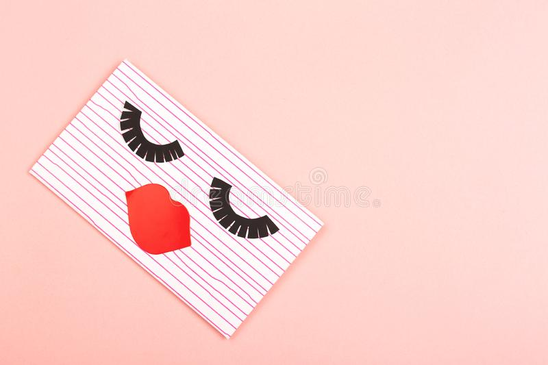 Envelope on pink background. Creative love or Valentine day background made with cute envelope. Eye lashes and red lips looklike a woman face. Love letter or stock photos