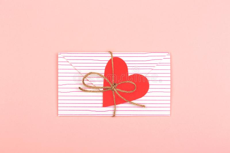 Envelope on pink background. Creative love or Valentine day background made with cute envelope, heart shape paper and rope. Love letter or message concept stock photography