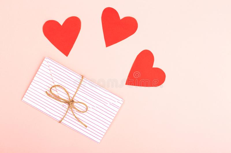 Envelope on pink background. Creative love or Valentine day background made with cute envelope, heart shape paper and rope. Love letter or message concept royalty free stock image