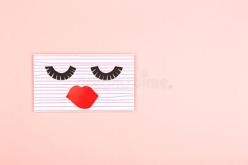 Envelope on pink background. Creative love or Valentines day background made with cute envelope. Eye lashes and red lips looklike a woman face. Love letter or royalty free stock images