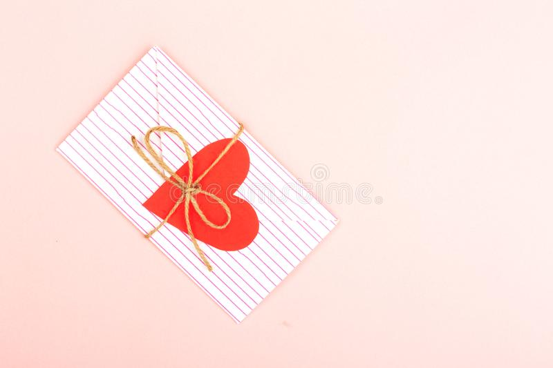 Envelope on pink background. Creative love or Valentines day background made with cute envelope, heart shape paper and rope. Love letter or message concept royalty free stock photography