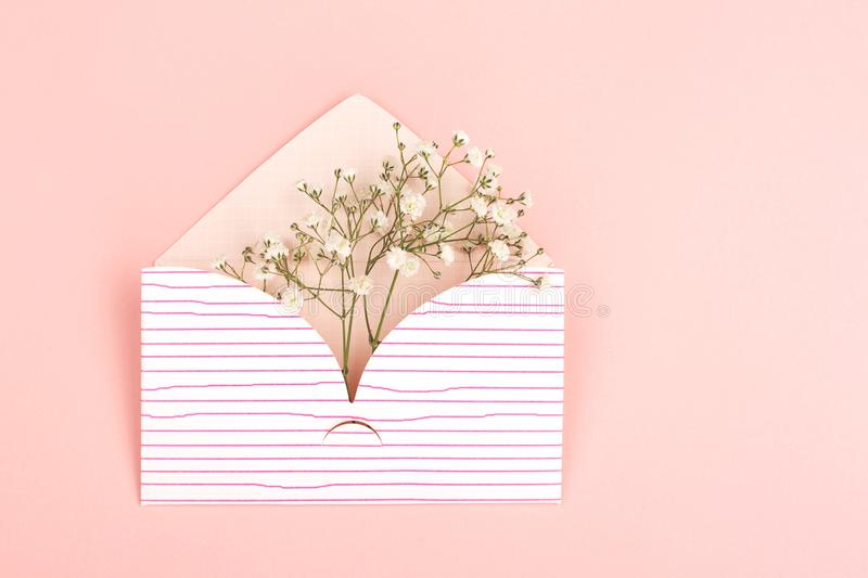 Envelope on pink background. International women`s day, spring or love concept. Background made with cute envelope and baby`s breath flowers. Pastel pink royalty free stock photo