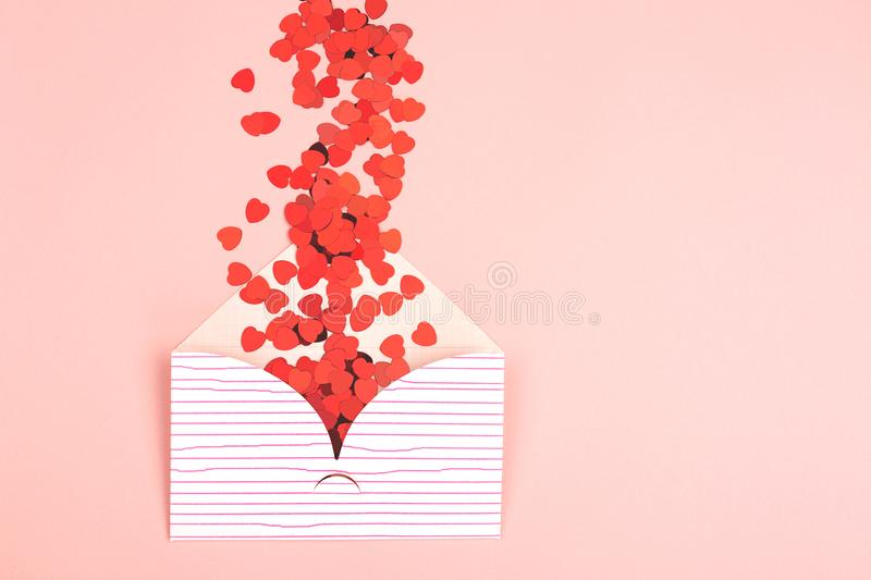 Envelope on pink background. Love or Valentine day background made with cute envelope and red heart shape confetti. Love letter or message concept. Pastel pink royalty free stock photo
