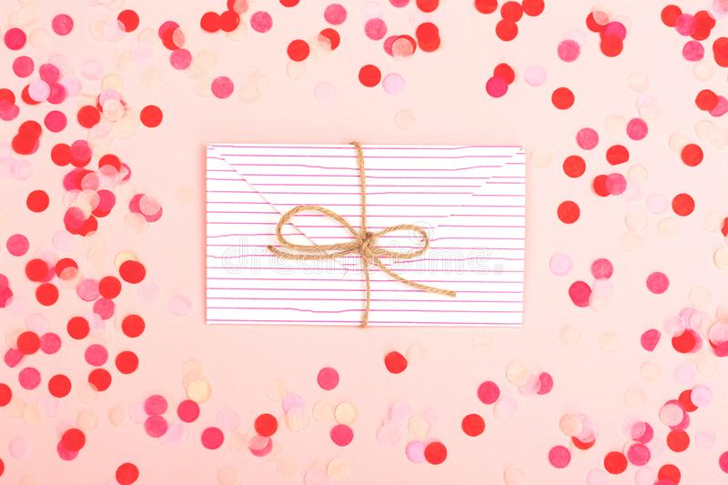 Envelope on pink background. Love or Valentines day background made with cute envelope and red confetti. Love letter or message concept. Pastel pink backdrop stock photos
