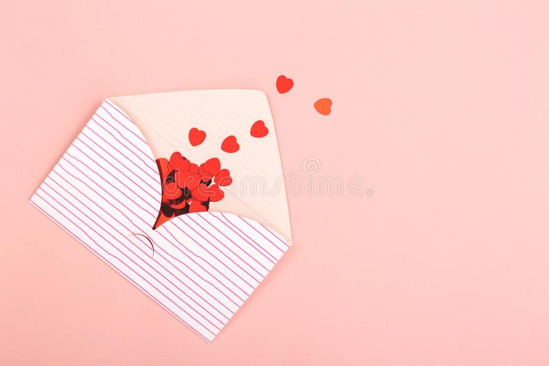 Envelope on pink background. Love or Valentines day background made with cute envelope and red heart shape confetti. Love letter or message concept. Pastel pink royalty free stock images
