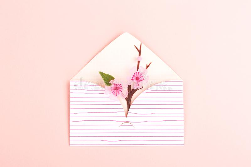 Envelope on pink background. Spring background made with cute envelope with cherry blossom branch. Pastel pink backdrop. Flat-lay, top view. Copy space for your stock photos