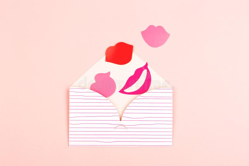 Envelope on pink background. Valentine day background made with cute envelope, red and pink lips. Love letter concept. Pastel pink backdrop. Flat-lay, top view royalty free stock image