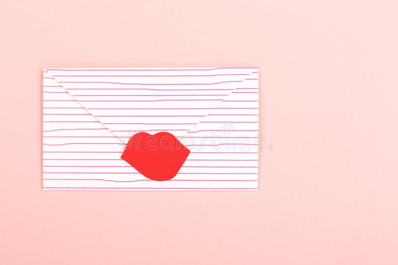 Envelope on pink background. Valentine day background made with cute envelope, sealed with red lipstick kiss. Love letter concept. Pastel pink backdrop. Flat-lay stock photography
