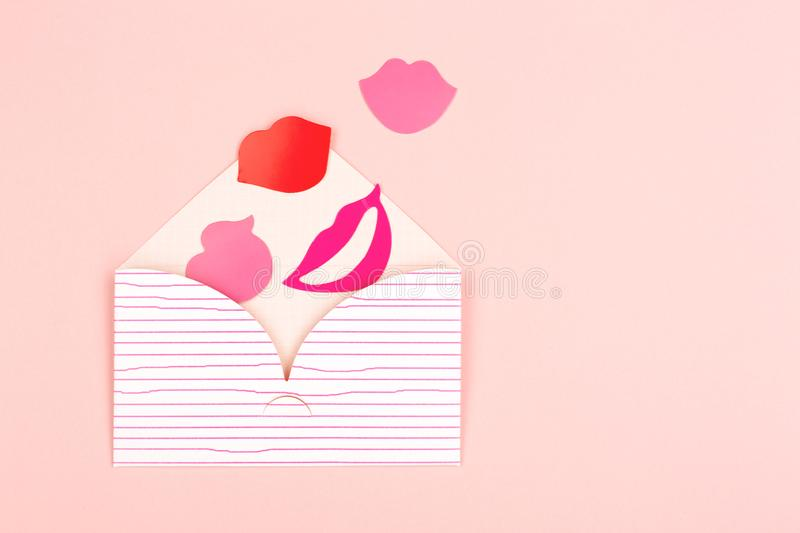 Envelope on pink background. Valentine background made with cute envelope, red and pink lips. Love letter concept. Pastel pink backdrop. Flat-lay, top view. Copy stock photo