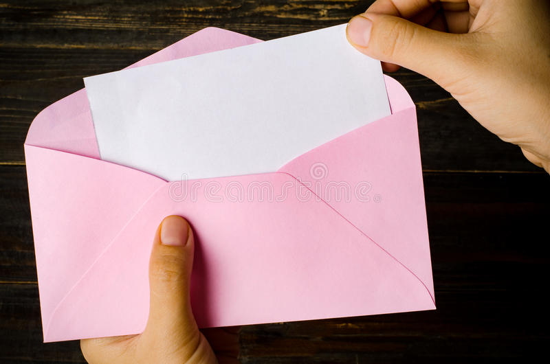 Envelope. Pink envelope and blank white card holding by hand stock photography