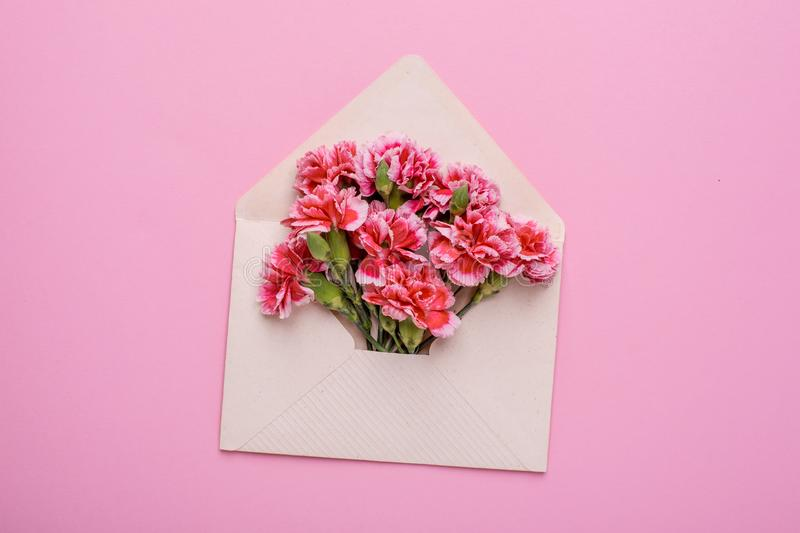 Envelope with pink flowers on a pink background royalty free stock image