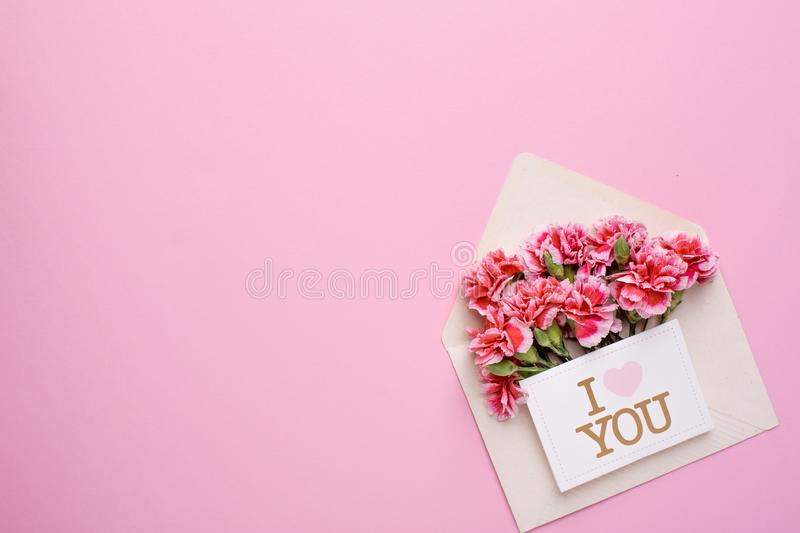 An envelope with pink flowers and a card I love you on a pink background. Top view stock photo