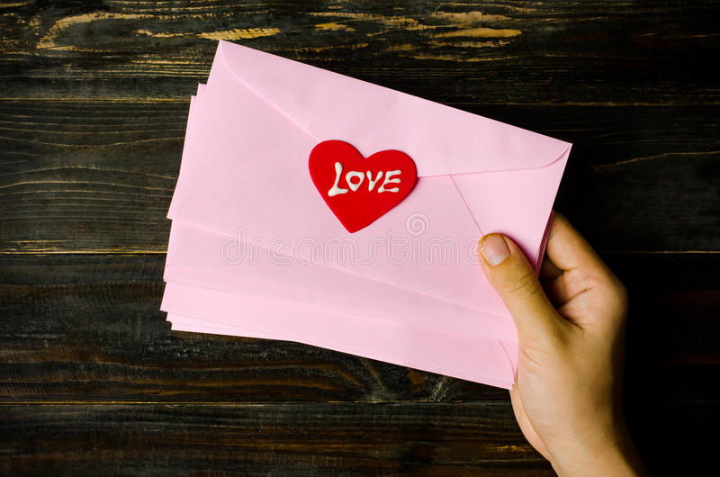 Envelope. Pink envelope with red heart holding by hand stock photography