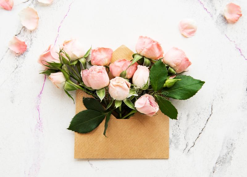 Envelope and pink roses. On a white marble background royalty free stock photography