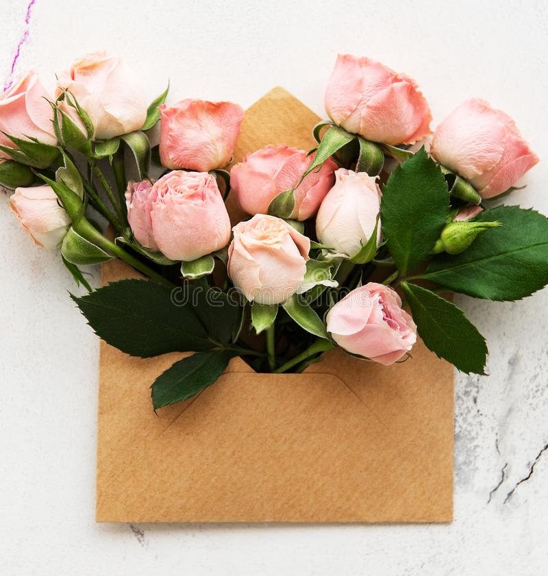 Envelope and pink roses. On a white marble background royalty free stock photos