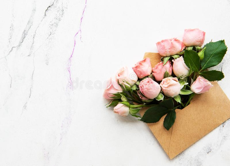 Envelope and pink roses. On a white marble background royalty free stock image