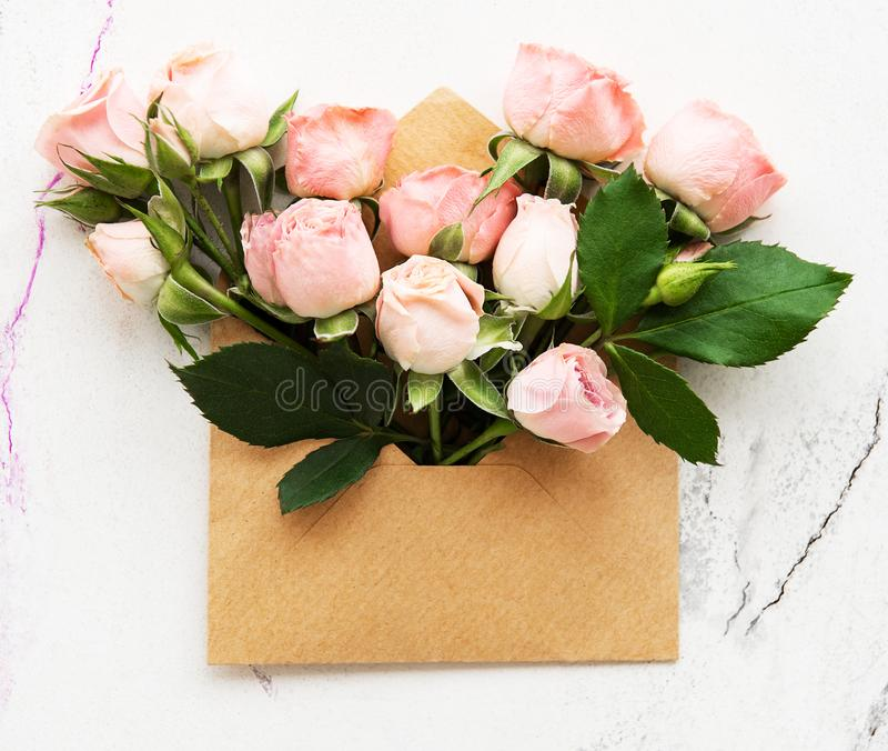 Envelope and pink roses. On a white marble background stock photography