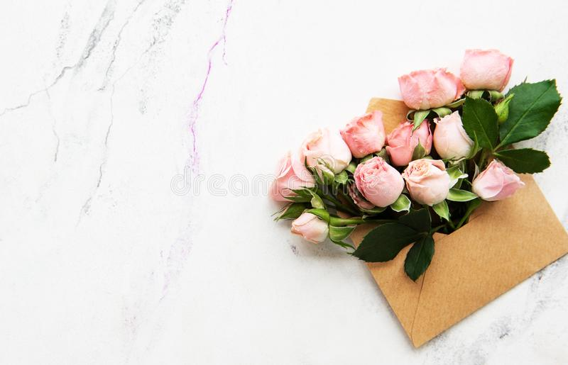 Envelope and pink roses. On a white marble background stock images